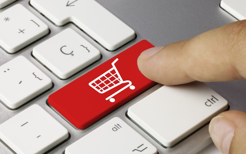 Finger points to button with shopping trolley