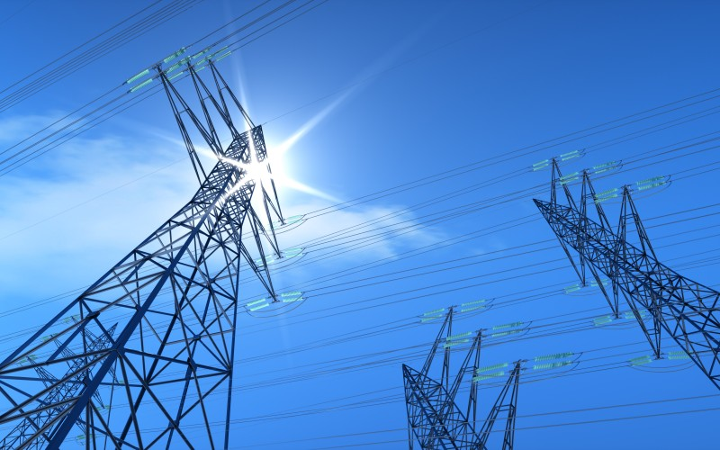 Transmission tower with blue sky and sun
